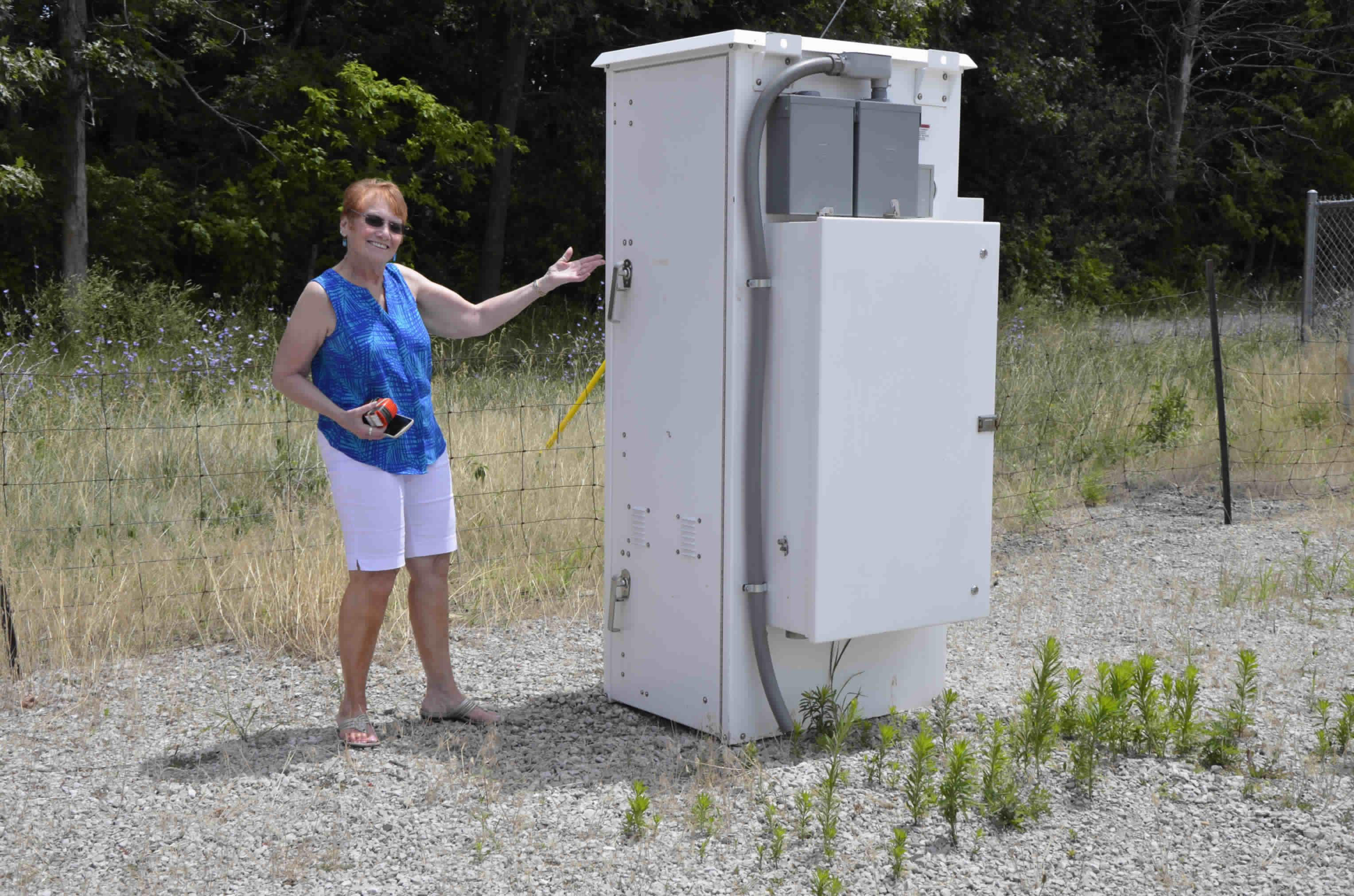 Carole Burke, WB9RUS, Vice President of the Fort Wayne Radio Club (FWRC) with DDB Inc. outside equipment enclosure recently donated by Mike Peters of Peters Broadcast Engineering.